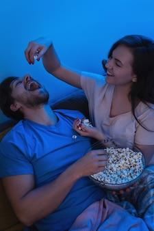 Casal jovem e feliz comendo pipoca e assistindo filme
