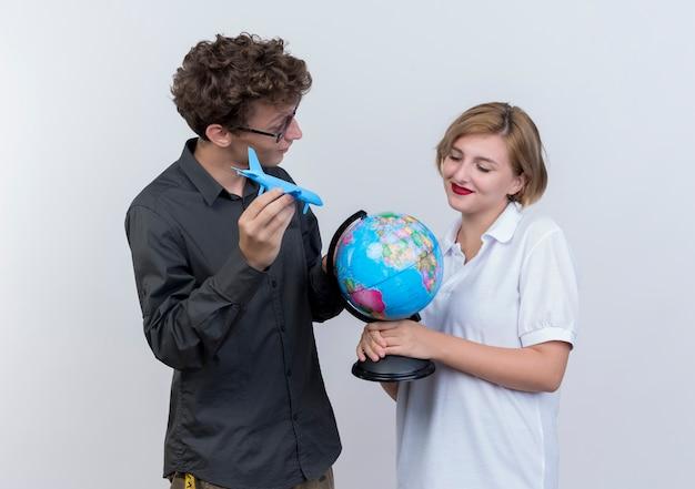 Casal jovem e feliz de turistas, homem e mulher segurando um avião de brinquedo globo e pé juntos sobre uma parede branca
