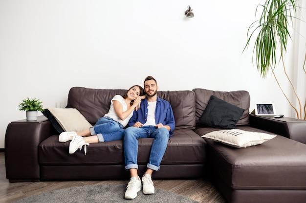 Casal jovem e feliz e sonhador em roupa casual, sentado no sofá de couro e curtindo a vida em um apartamento aconchegante, com a garota apoiando a cabeça no ombro do namorado