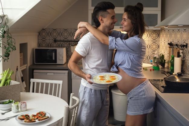 Casal jovem e feliz esperando um bebê. marido e esposa grávida na cozinha durante a hora do café da manhã.