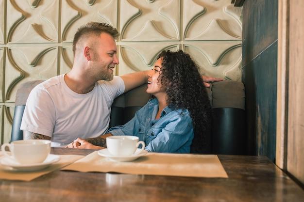 Casal jovem e feliz está bebendo café e sorrindo enquanto está sentado no café