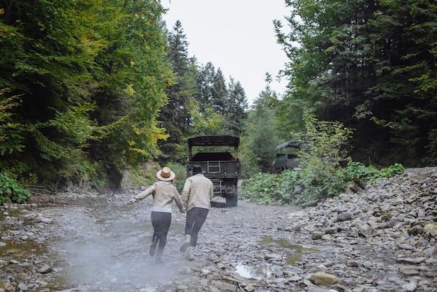 Casal jovem e fofo correndo atrás de um caminhão em uma estrada florestal