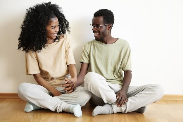 Casal jovem e fofo de pele escura usando camisetas, calças e meias casuais semelhantes, juntos em casa