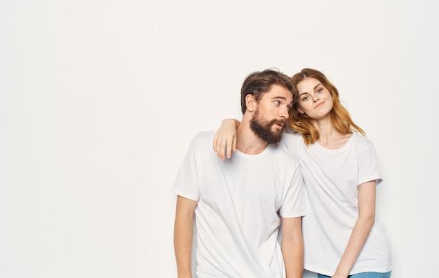 Casal jovem e fofo em jeans e camisetas brancas abraça emoções isoladas de fundo