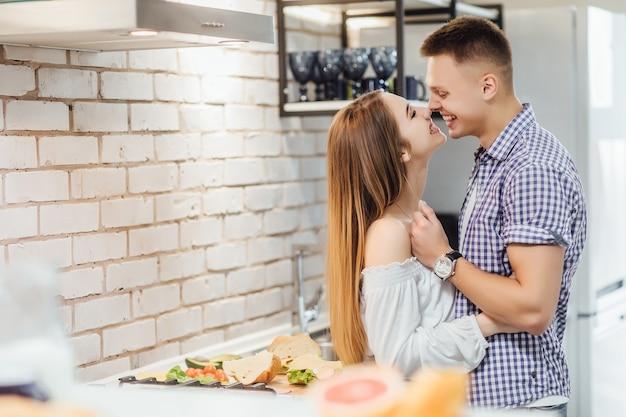 Casal jovem e fofo se divertindo juntos na cozinha, se abraçando e se beijando.