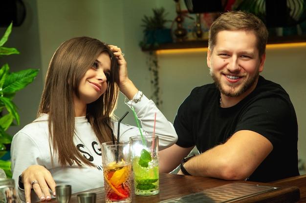Casal jovem e fofo se divertindo no bar com coquetéis alcoólicos