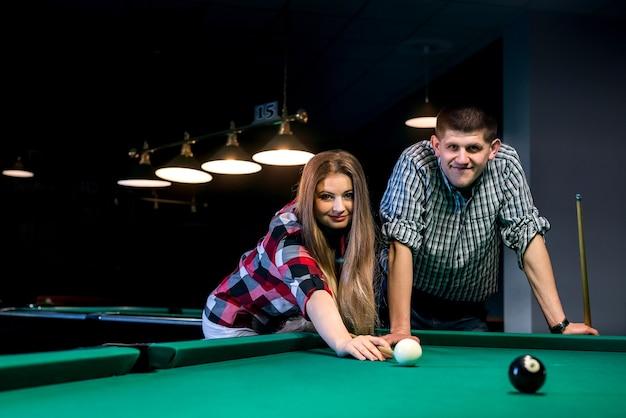 Casal jovem e lindo jogando bilhar em bar
