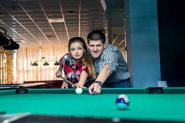 Casal jovem e lindo jogando bilhar juntos