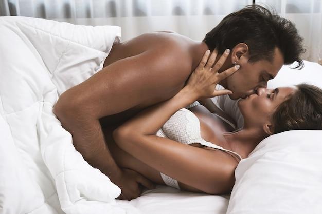Casal jovem e lindo se abraçando, deitado na cama