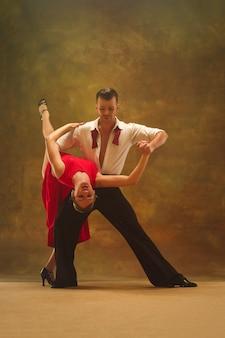 Casal jovem e moderno flexível dançando tango no estúdio. retrato da moda de atraente casal dançando. homem e mulher. paixão. ame. pele perfeita facial e maquiagem. emoções humanas - amor e paixão