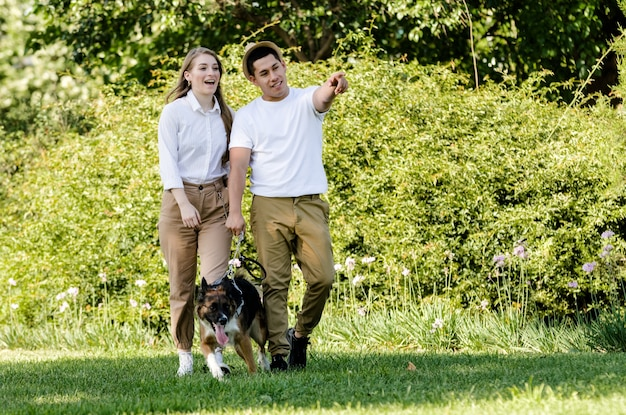 Casal jovem e moderno passeando e brincando com seu cachorro border collie em um parque