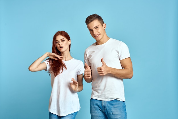 Casal jovem e mulher usando camisetas brancas em um fundo azul claro
