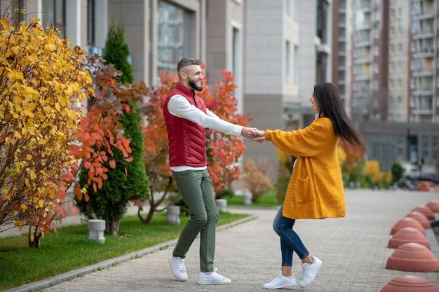 Casal jovem e simpático de mãos dadas enquanto aproveitam o momento juntos