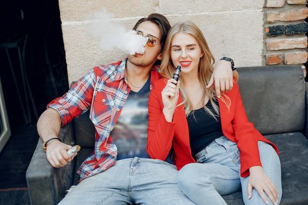 Casal jovem elegante com vape em um café