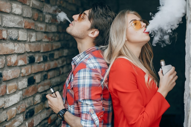 Casal jovem elegante com vape em uma cidade