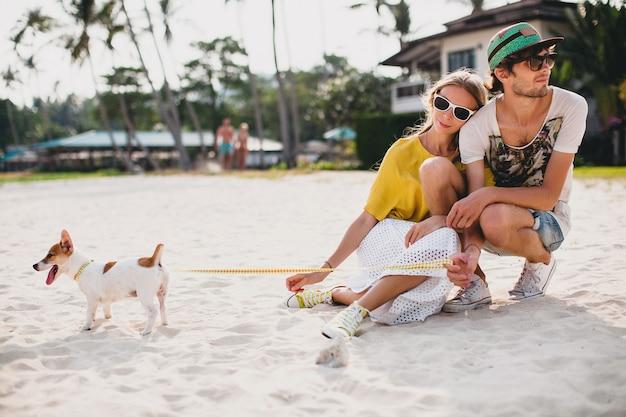 Casal jovem elegante e hippie apaixonado andando e brincando com um cachorro em uma praia tropical