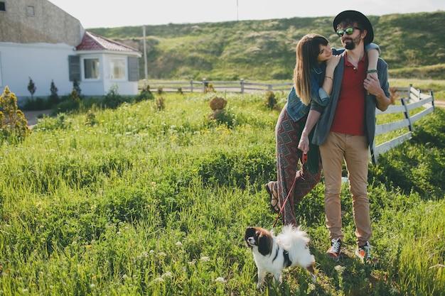 Casal jovem elegante e hippie apaixonado, caminhando com um cachorro no campo