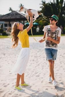 Casal jovem elegante e moderno apaixonado, andando e brincando com o cachorro na praia