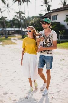 Casal jovem elegante e moderno apaixonado, andando e brincando de cachorro