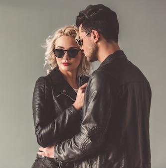 Casal jovem elegante em jaquetas de couro e óculos de sol