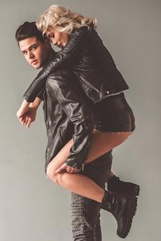 Casal jovem elegante em jaquetas de couro em fundo cinza