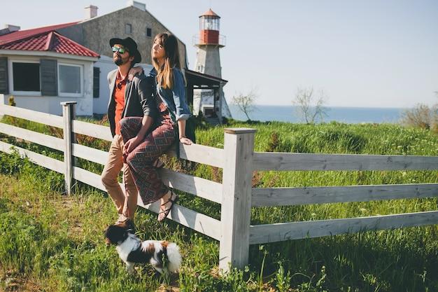 Casal jovem elegante hippie apaixonado, caminhando com um cachorro no campo, estilo boho de verão