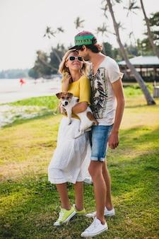 Casal jovem elegante hippie apaixonado segurando um cachorro no parque tropical, sorrindo e se divertindo durante as férias