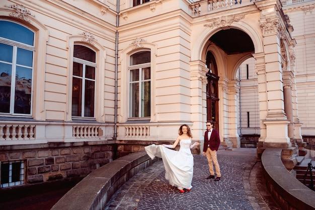 Casal jovem elegante no fundo da arquitetura requintada do antigo palácio