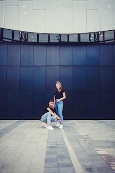 Casal jovem elegante perto de parede azul