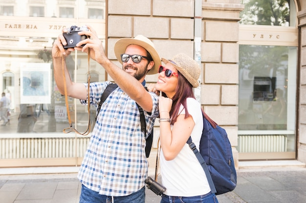 Casal jovem elegante tendo selfie na câmera