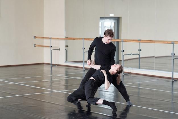 Casal jovem em calças pretas e camisetas treinando um dos exercícios de dança durante a aula em um grande estúdio moderno de dança
