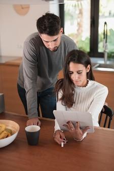 Casal jovem em casa usando o tablet