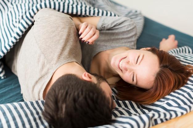Casal jovem em cobertores dentro de casa