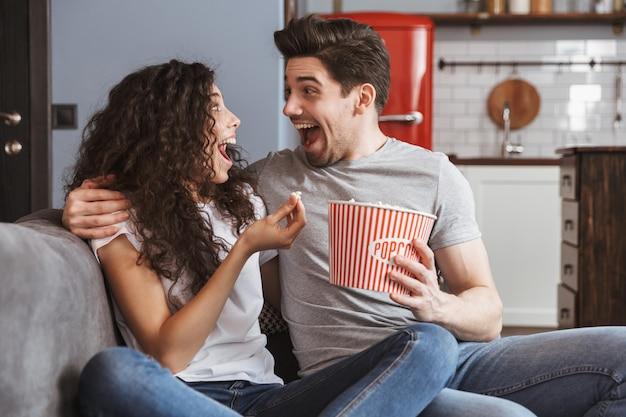 Casal jovem em êxtase, homem e mulher, sentados no sofá em casa comendo pipoca no balde