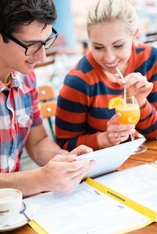 Casal jovem em um café de rua bebendo café e suco enquanto assiste fotos de feriados