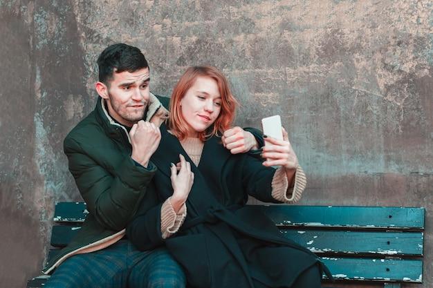 Casal jovem emocional alegre sentado no banco e fazendo selfie. duas pessoas felizes amam a história na rua