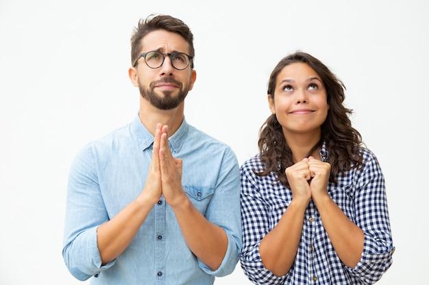 Casal jovem emocional rezando juntos