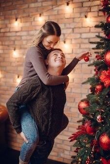 Casal jovem enfeitando a árvore de natal em casa