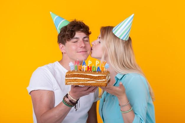Casal jovem engraçado em tampas de papel e com um bolo faz uma cara de bobo e deseja feliz aniversário em pé contra uma parede amarela. conceito de parabéns e brincadeira.