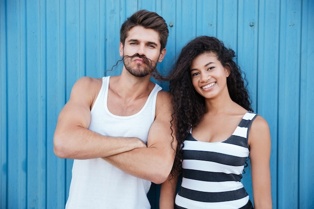 Casal jovem engraçado fazendo bigode com cabelo e se divertindo em uma parede azul