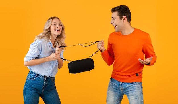 Casal jovem engraçado lutando por alto-falante sem fio, ouvindo música no estilo colorido