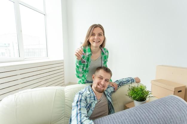 Casal jovem engraçado positivo segurando as chaves de um novo apartamento em pé na sala de estar. conceito de hipoteca de inauguração de casa e família.