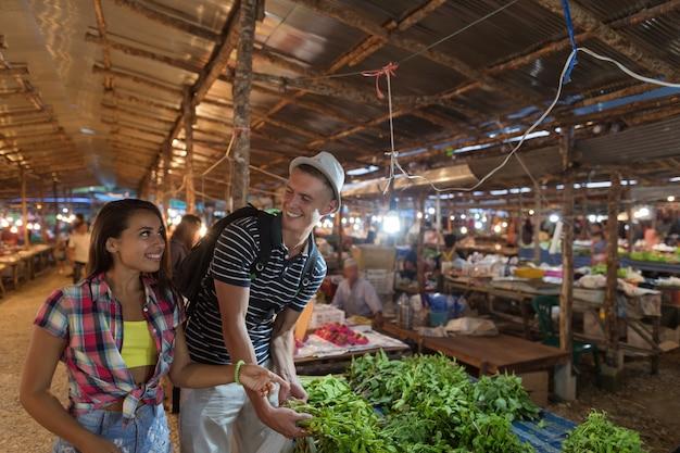 Casal jovem escolhe ervas no mercado de vegetais homem feliz sorrindo e compras de mulher juntos no stre