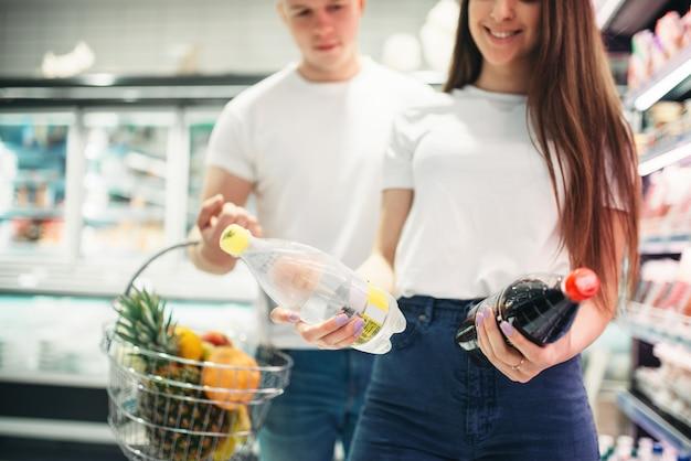 Casal jovem escolhendo frutas frescas no supermercado