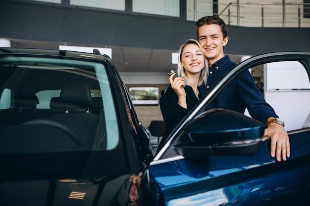 Casal jovem, escolhendo um carro em uma sala de show de carro