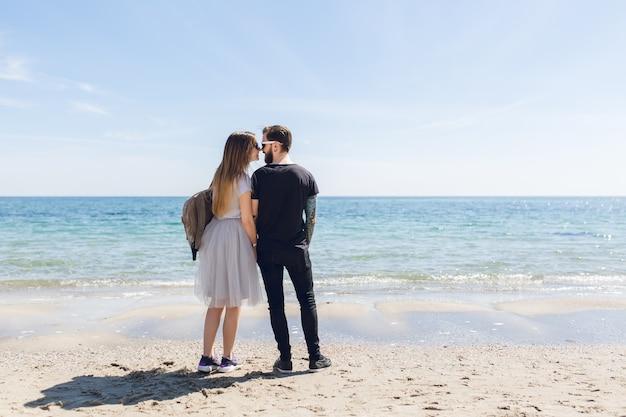 Casal jovem está em pé na praia perto do mar