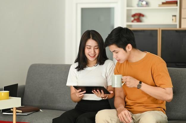 Casal jovem está navegando na internet com um laptop enquanto está sentado no sofá em casa