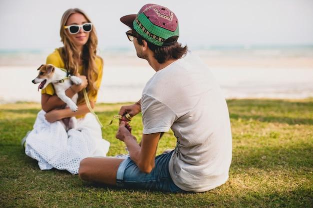 Casal jovem estiloso e hippie apaixonado andando e brincando com o cachorro
