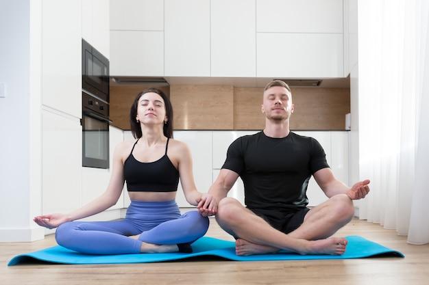 Casal jovem fazendo ioga em casa, duas pessoas sentadas no chão em posição de lótus na cozinha