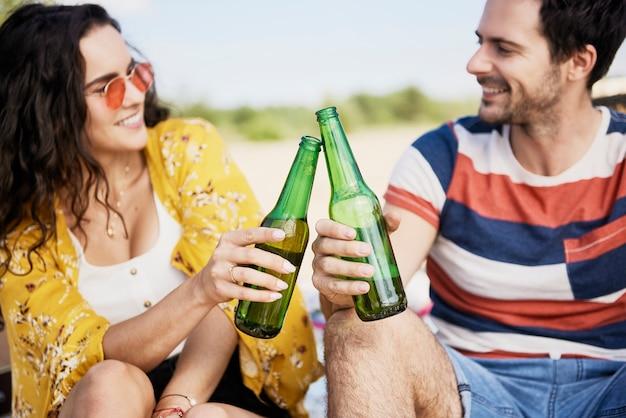 Casal jovem fazendo um brinde de comemoração com garrafas de cerveja na praia